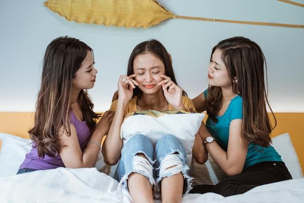 Jovens mulheres asiáticas conversando e consolando o amigo triste no quarto