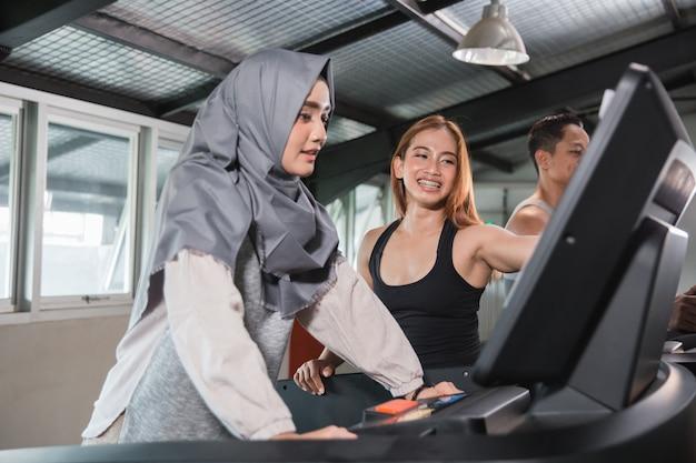 Jovens mulheres asiáticas hijab correr na esteira