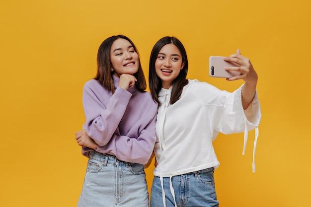 Jovens mulheres asiáticas morenas descoladas em moletons elegantes tirando uma selfie, sorrindo sinceramente e fazendo pose de bom humor na parede laranja
