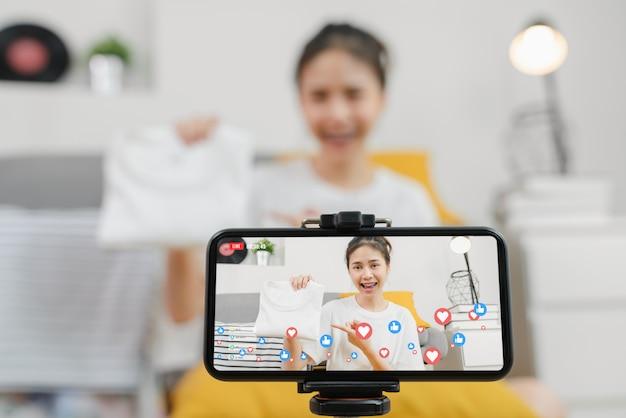 Jovens mulheres asiáticas mostrando roupas e venda on-line no social com smartphone para clientes em casa. conceito de tecnologia de rede.