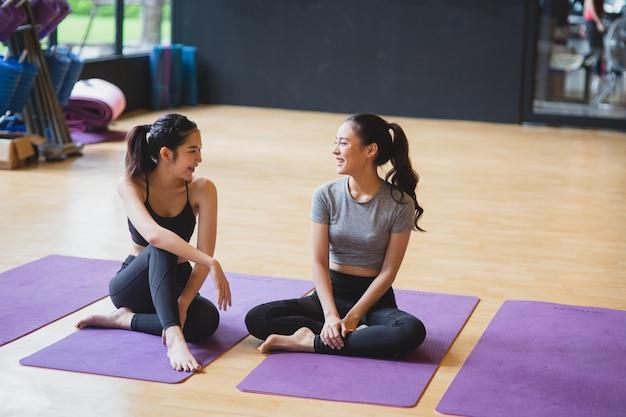 Jovens mulheres asiáticas na aula de ioga, sorrindo e conversam juntos, estilo de vida saudável no conceito de clube de fitness
