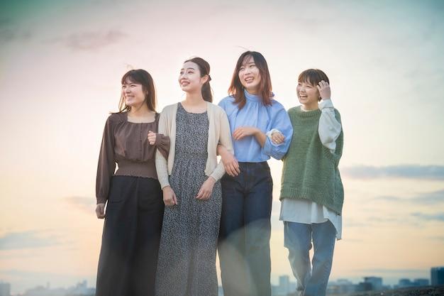 Jovens mulheres asiáticas olhando para um cenário distante à noite