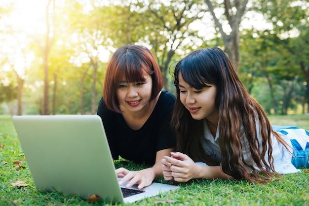 Jovens mulheres asiáticas pernas na grama verde com laptop aberto