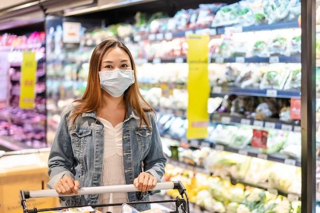 Jovens mulheres asiáticas usando máscara cirúrgica comprando vegetais frescos em uma mercearia no supermercado durante surto de coronavírus