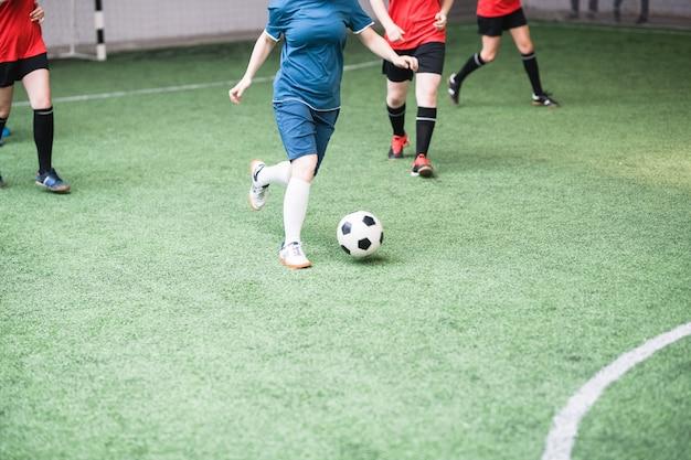 Jovens mulheres ativas com uniforme esportivo vermelho e azul atacando a bola durante o jogo de futebol no campo
