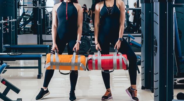 Jovens mulheres atléticas que treinam com os sacos de areia no cinza.