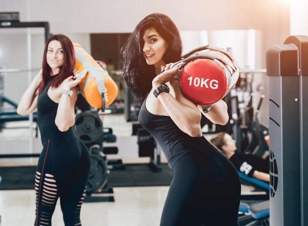 Jovens mulheres atléticas que treinam com sacos de areia