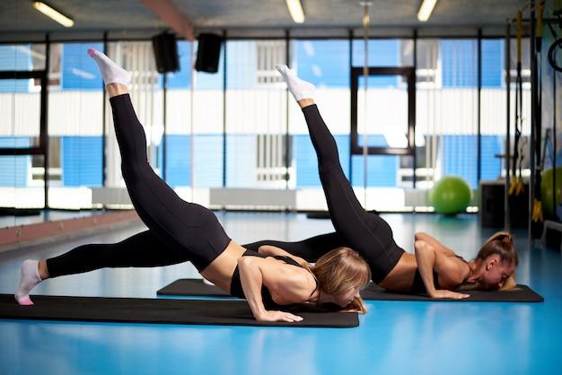 Jovens mulheres atléticas um treinamento no gym.