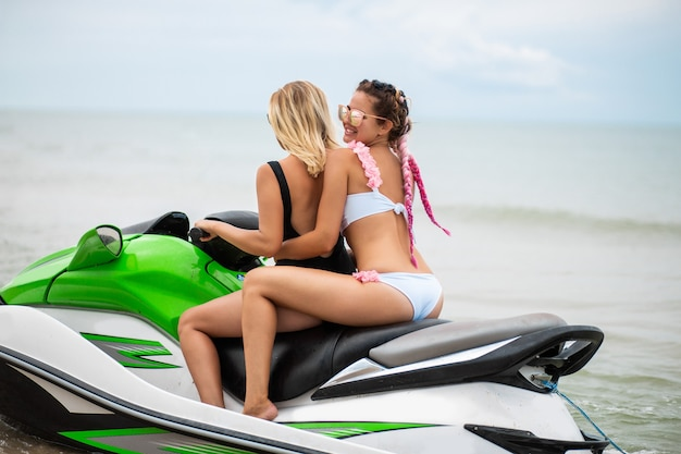Jovens mulheres atraentes com corpo esguio em biquíni estiloso se divertindo na moto aquática, amigos nas férias de verão, esporte ativo