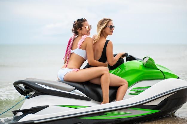 Jovens mulheres atraentes com corpo esguio sexy em biquíni estiloso se divertindo em uma scooter aquática, amigos nas férias de verão, esporte ativo