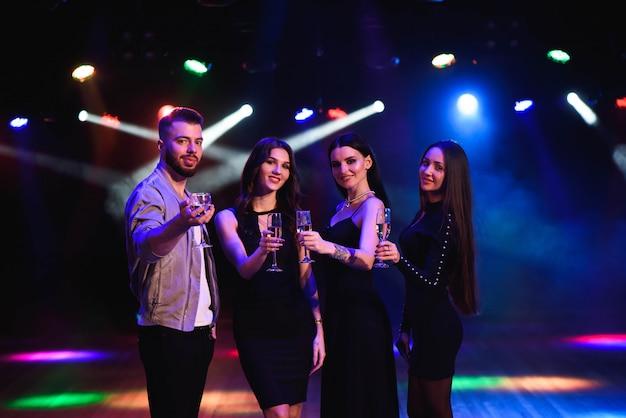 Jovens mulheres atraentes e homem comemorando uma festa, bebendo champanhe e dançar