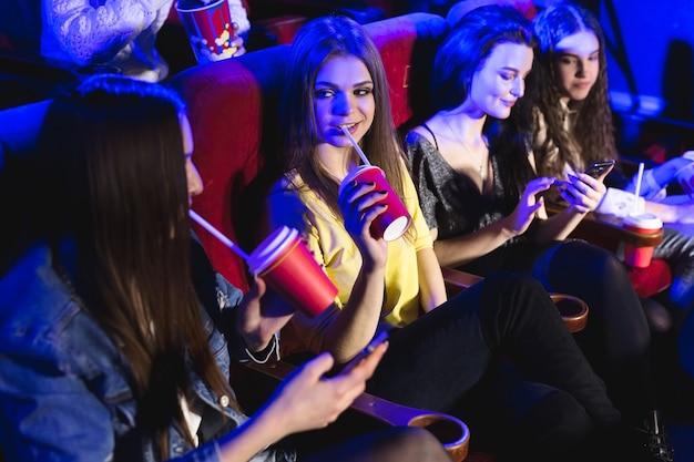 Jovens mulheres bonitas bebem em um copo no cinema e assistem a um filme