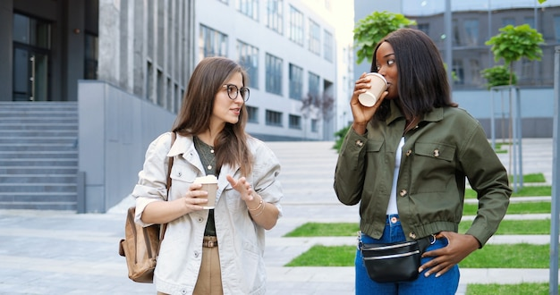 Jovens mulheres bonitas de raça mista, melhores amigas conversando animadamente e caminhando com xícaras de café para viagem e nas ruas da cidade.