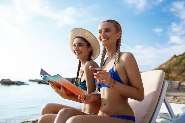 Jovens mulheres bonitas em trajes de banho sorrindo, procure revista à beira-mar