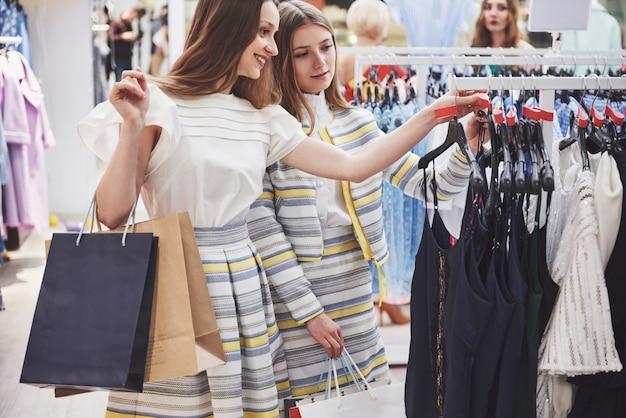 Jovens mulheres bonitas no mercado semanal de roupas. melhores amigas têm tempo livre se divertindo e fazendo compras