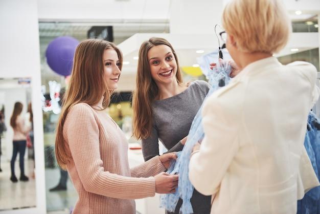 Jovens mulheres bonitas no mercado semanal de roupas. o gerente da loja ajuda o comprador. melhores amigas que compartilham o tempo livre se divertindo e fazendo compras