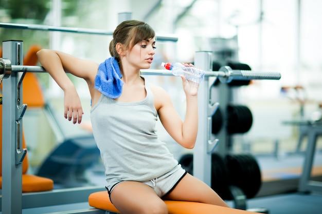 Jovens mulheres bonitas no sportswear com toalha, sentado no banco durante o treino, sentindo-se cansado e bebendo água no ginásio
