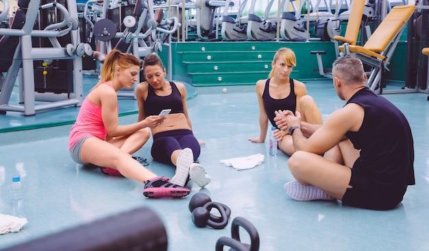 Jovens mulheres bonitas olhando para o smartphone enquanto um casal de amigos conversando sentado no chão da academia