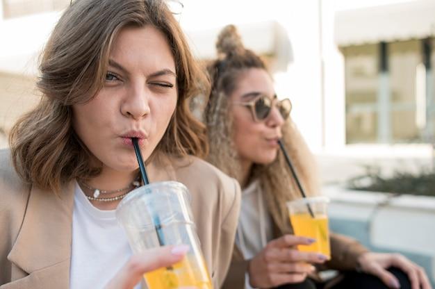 Jovens mulheres bonitas que bebem suco de laranja