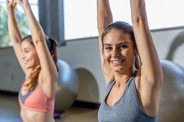 Jovens mulheres bonitas que esticam em um gym.