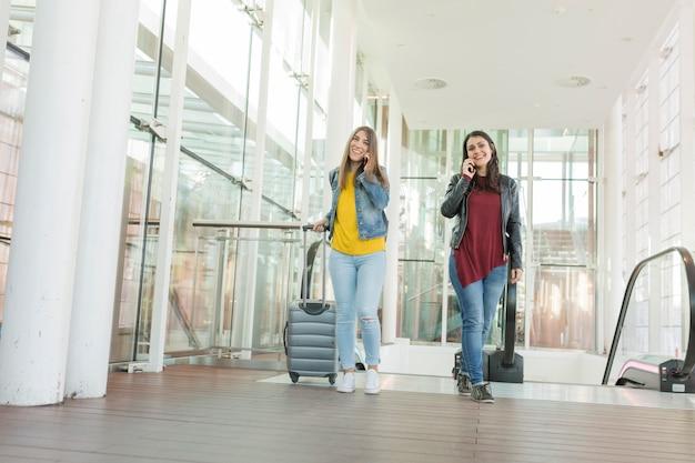 Jovens mulheres bonitas que falam em seu telefone móvel e no sorriso. conceito de viagens no aeroporto, ela está subindo escadas com um carrinho. amigos e estilo de vida