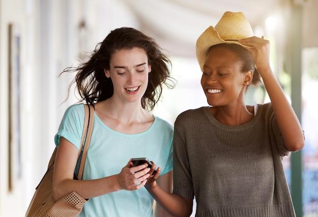 Jovens mulheres caminhando juntos usando o celular