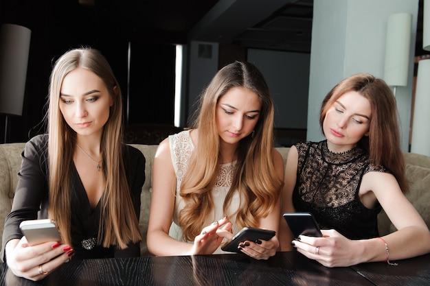 Jovens mulheres caucasianas usando telefone e dizendo não para a vida