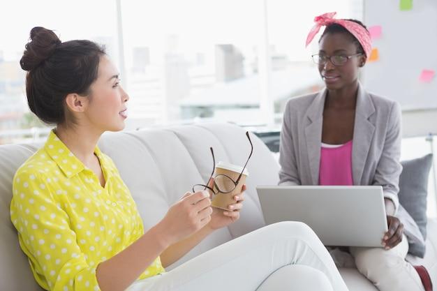 Jovens mulheres criativas conversando no sofá
