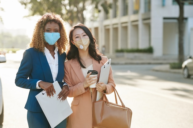 Jovens mulheres de negócios alegres com máscaras protetoras em pé ao ar livre com pranchetas após uma importante reunião de negócios