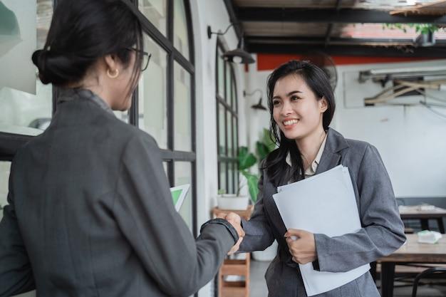 Jovens mulheres de negócios asiáticas se encontrando em um café e apertam as mãos