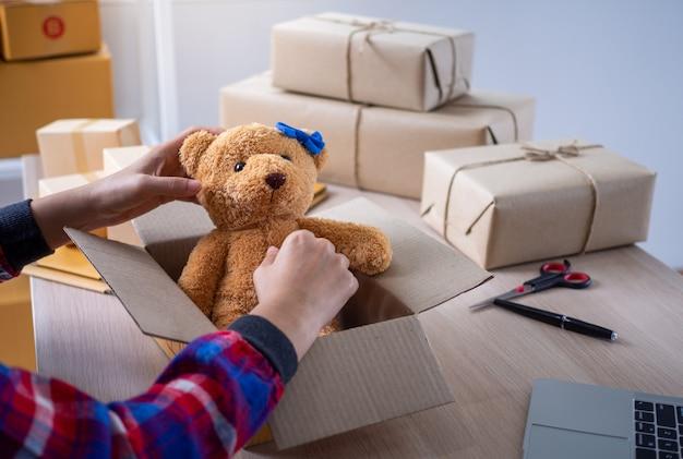 Jovens mulheres de negócios estão preparando caixas para entregar produtos a compradores on-line.