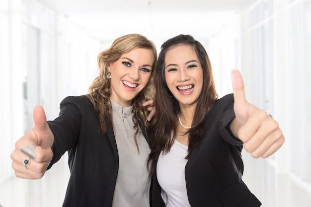 Jovens mulheres de negócios, fazendo os polegares para cima gesto vestindo blusa e blazer