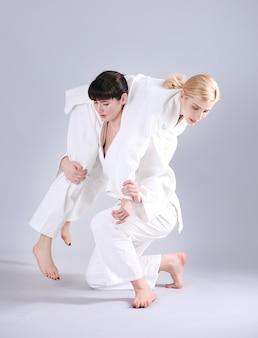 Jovens mulheres desportivas praticando artes marciais em fundo claro