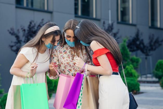 Jovens mulheres despreocupadas e felizes usam uma máscara carregando uma sacola de compras no conceito de volta às compras, novo estilo de vida de moda normal de verão após covid19.