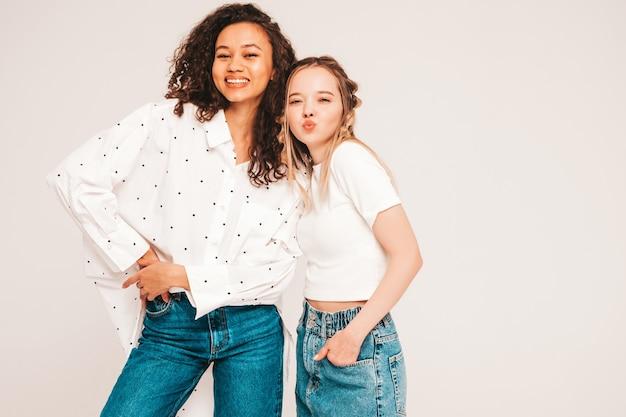 Jovens mulheres despreocupadas posando em uma parede cinza em um estúdio