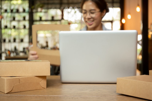 Jovens mulheres do negócio startup que trabalham no laptop com o pacote na tabela.