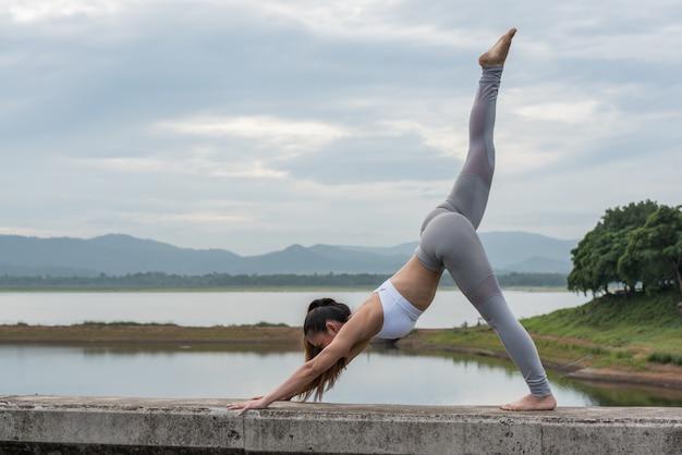 Jovens mulheres dos esportes que praticam a ioga na manhã pelo reservatório com fundo das montanhas.
