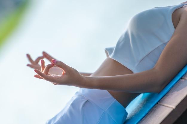 Jovens mulheres dos esportes que praticam a meditação da ioga a manhã pelo reservatório com fundo das montanhas.