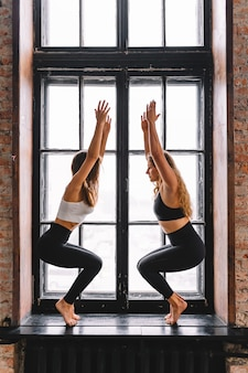 Jovens mulheres em alongamento pose de ioga