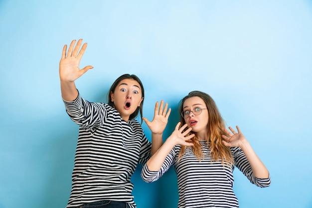 Jovens mulheres emocionais chocadas e assustadas isoladas na parede azul do estúdio
