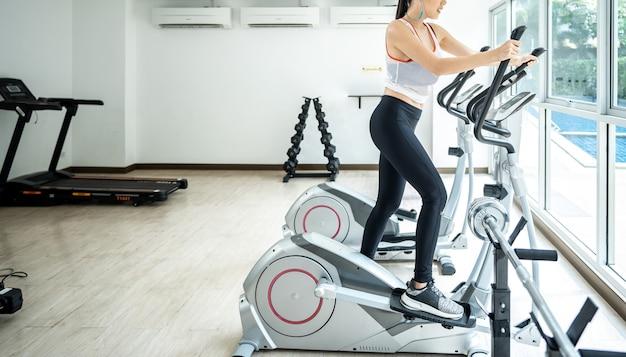 Jovens mulheres fazendo esporte ciclismo com a amiga na academia de fitness