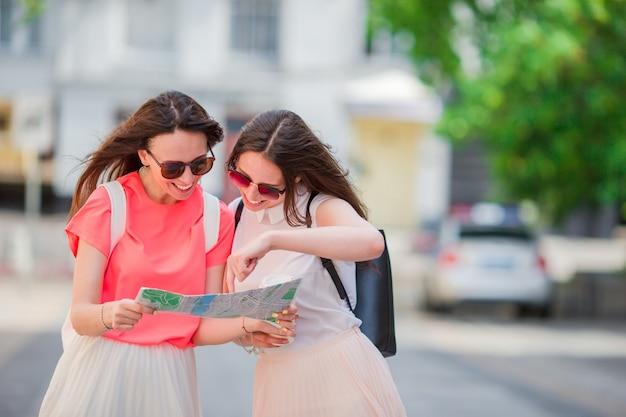 Jovens mulheres felizes com mapa turístico andando na rua europeia.