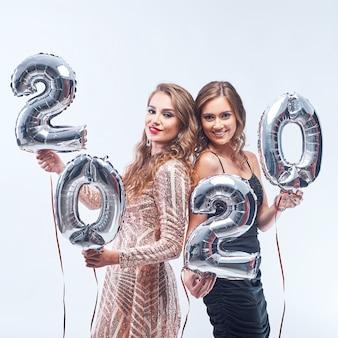 Jovens mulheres felizes com os balões 2020 metálicos no branco.