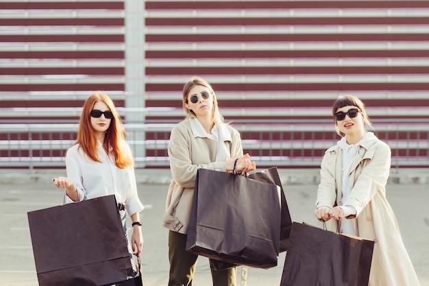 Jovens mulheres felizes com sacolas de compras, andando na rua.