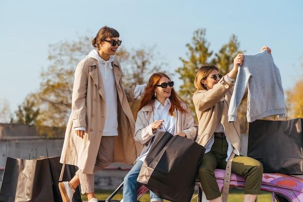 Jovens mulheres felizes com sacolas de compras se passando perto de um velho carro decorado