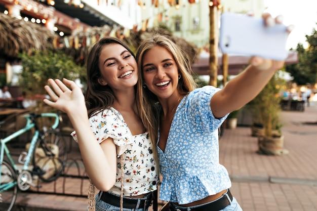 Jovens mulheres felizes em blusas florais elegantes sorriem sinceramente e tiram selfies ao ar livre