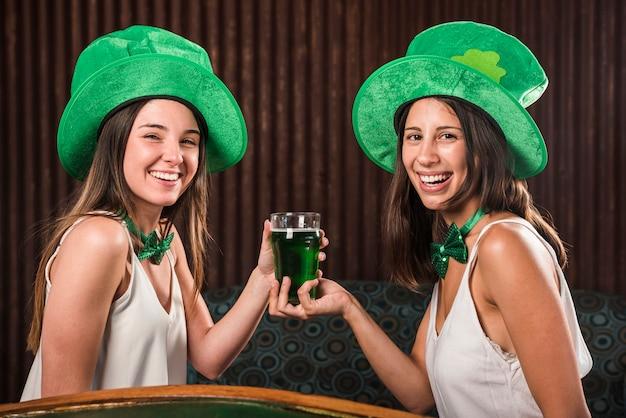 Jovens mulheres felizes que guardam o copo da bebida no canapé na sala