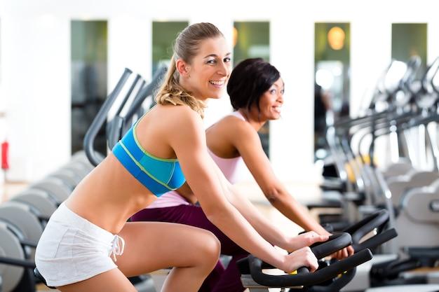 Jovens - mulheres girando na academia em bicicletas fitness