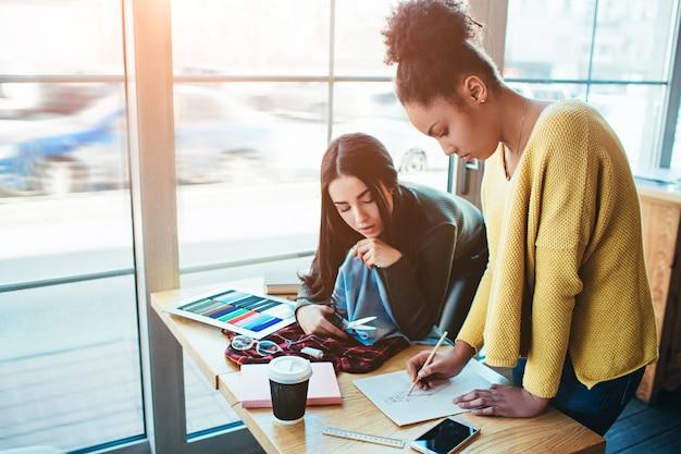 Jovens mulheres juntas e trabalhando no mesmo projeto de moda