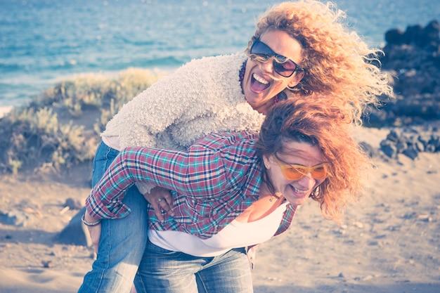Jovens mulheres lindas e loucas de caucasianos se seguem dando muitas risadas e se divertindo para amizades